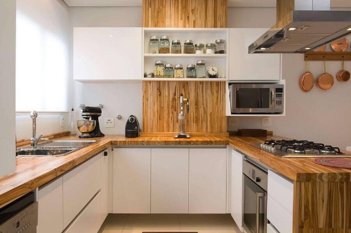 Cozinha em U com bancada de madeira e armários brancos.