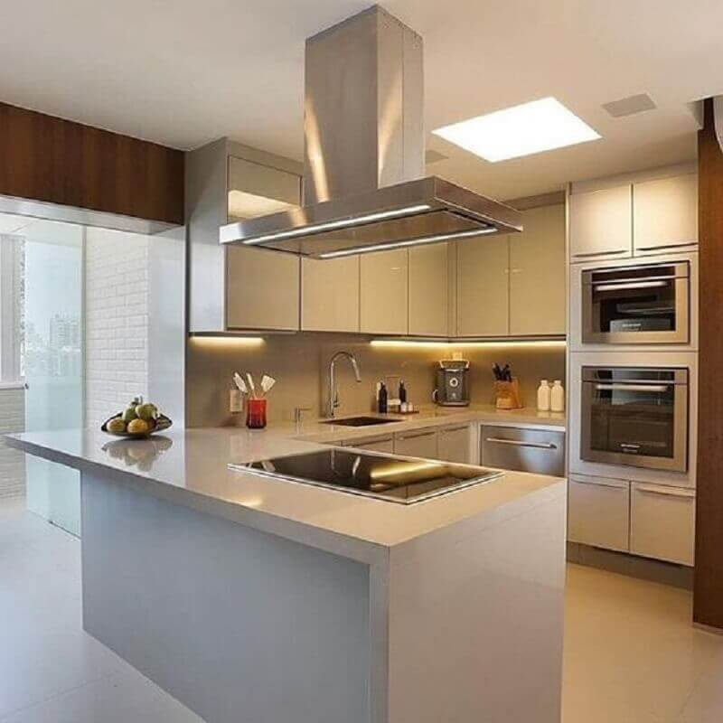 Cozinha em U com bancada branca e cooktop.