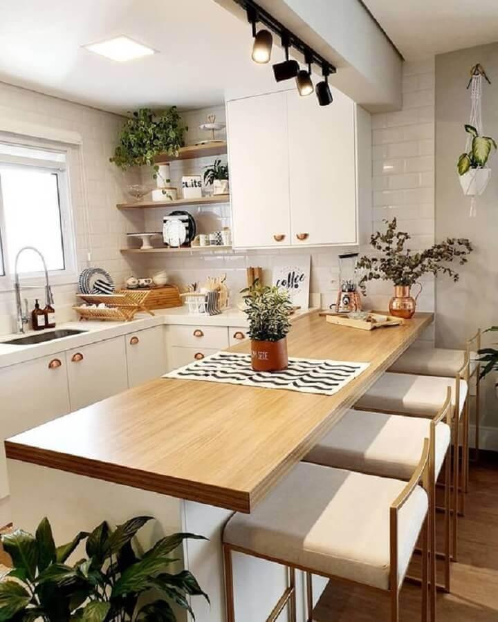 Cozinha em U com bancada de madeira e decoração escandinava.