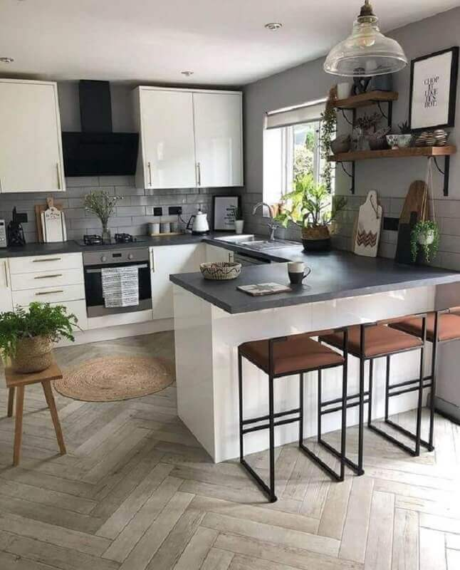 Cozinha em U com bancada de granito e armários brancos.