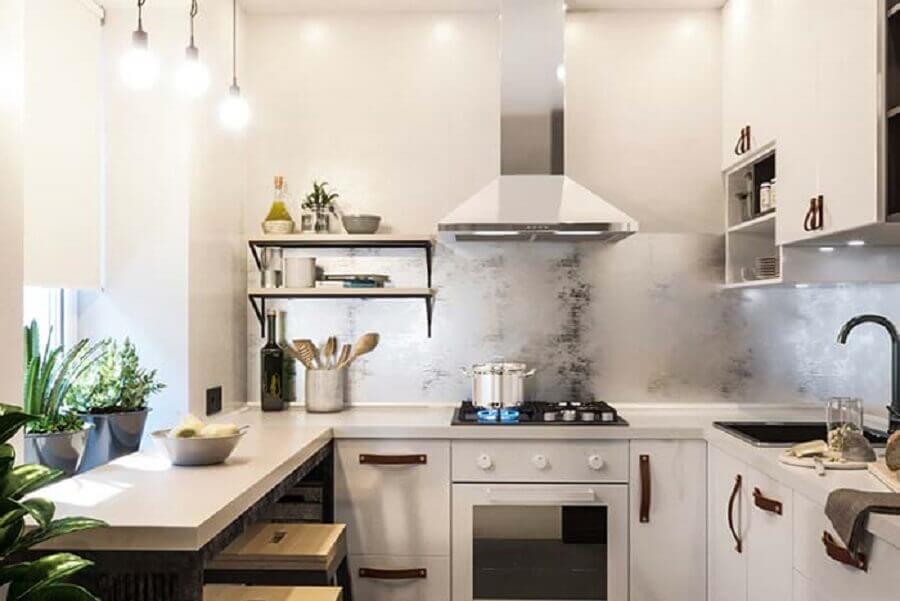 Cozinha em U com bancada com bancada de madeira e armários brancos.