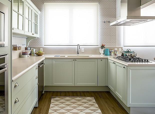 Cozinha em U com bancada de madeira branca e armários verde menta.