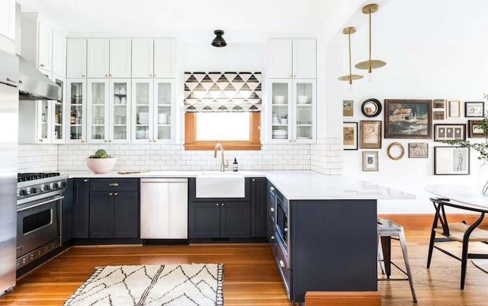 Cozinha em U com bancada de mármore e armários pretos e brancos.