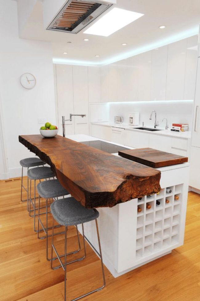 Cozinha em U com bancada de madeira rústica e armários minimalistas.