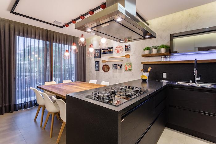 Cozinha em U com bancada de granito e armários pretos.
