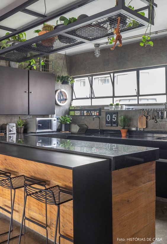 Cozinha em U com bancada de granito e parede de cimento queimado.