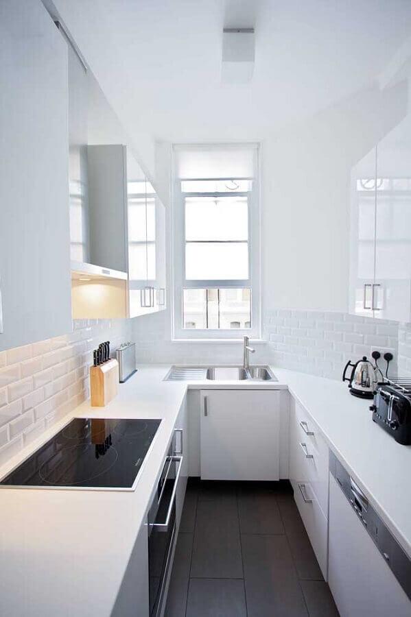 Cozinha em U pequena branca com cooktop.