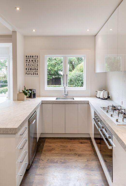 Cozinha em U pequena branca com bancada de mármore.