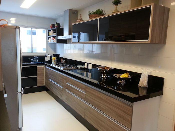 Cozinha em U pequena com armário de madeira e bancada de granito.