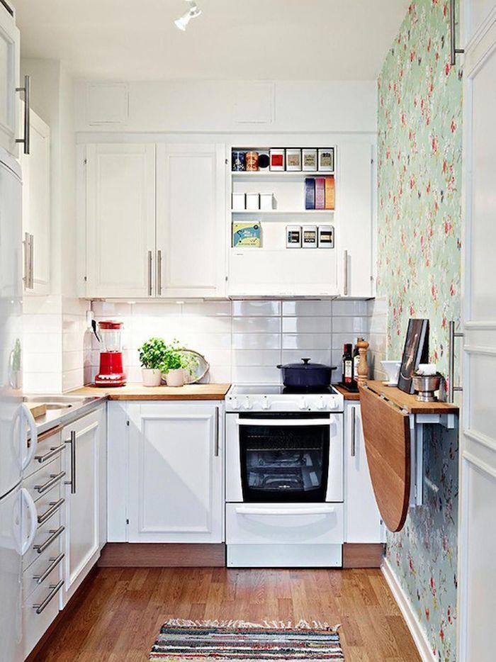 Cozinha em U pequena com mesa retrátil e papel de parede decorado.