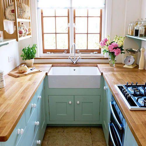 Cozinha em U pequena com armários verdes e bancada de madeira.