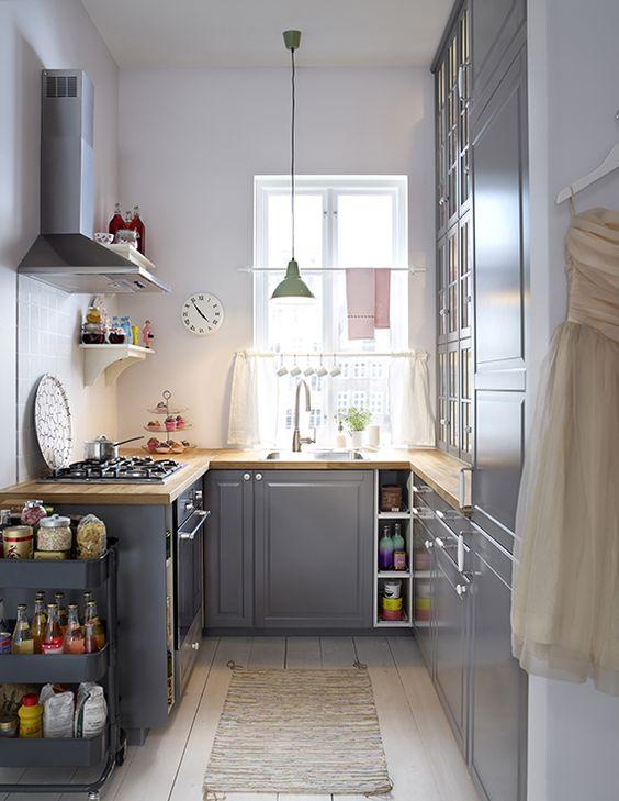 Cozinha em U pequena com armários cinzas.