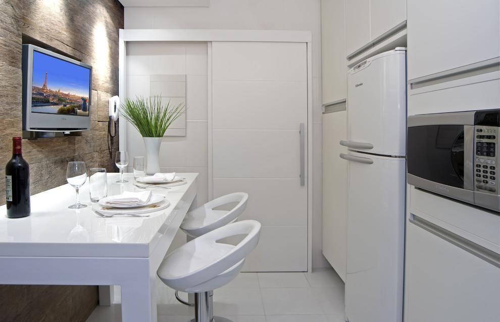 Decoração moderna com armário branco, mesa branca e parede com acabamento de madeira.