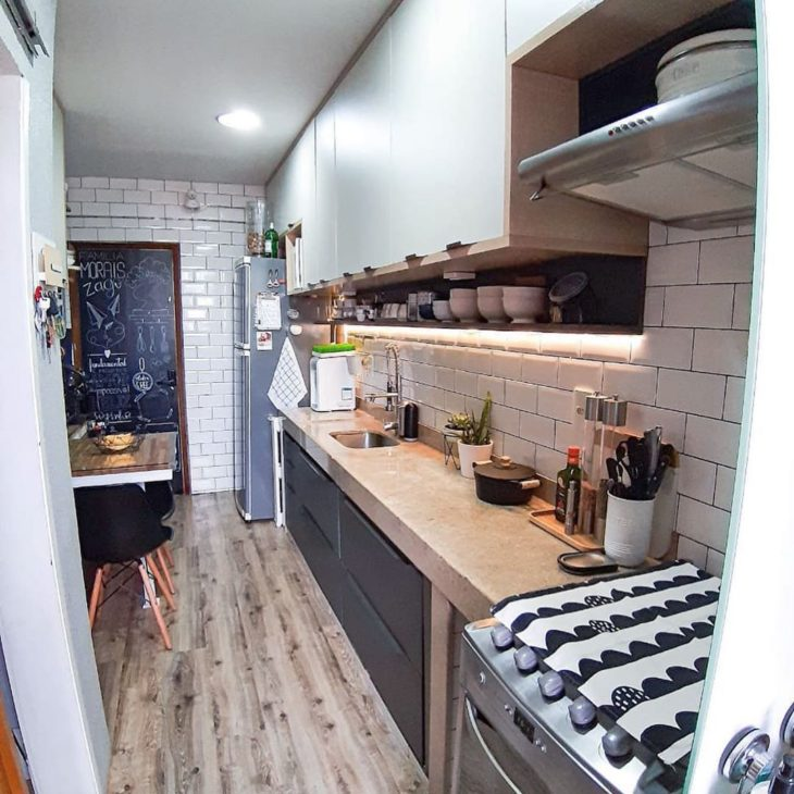 Decoração moderna com azulejo de tijolinho branco e armário preto.