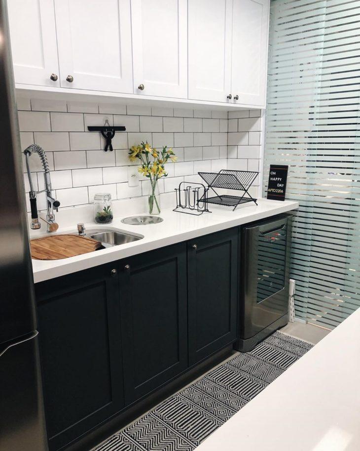 Decoração com azulejo de tijolinho branco e armário branco e preto.