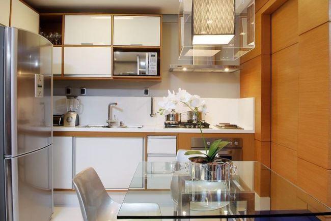 Decoração luxuosa com mesa de vidro e lustre moderna.