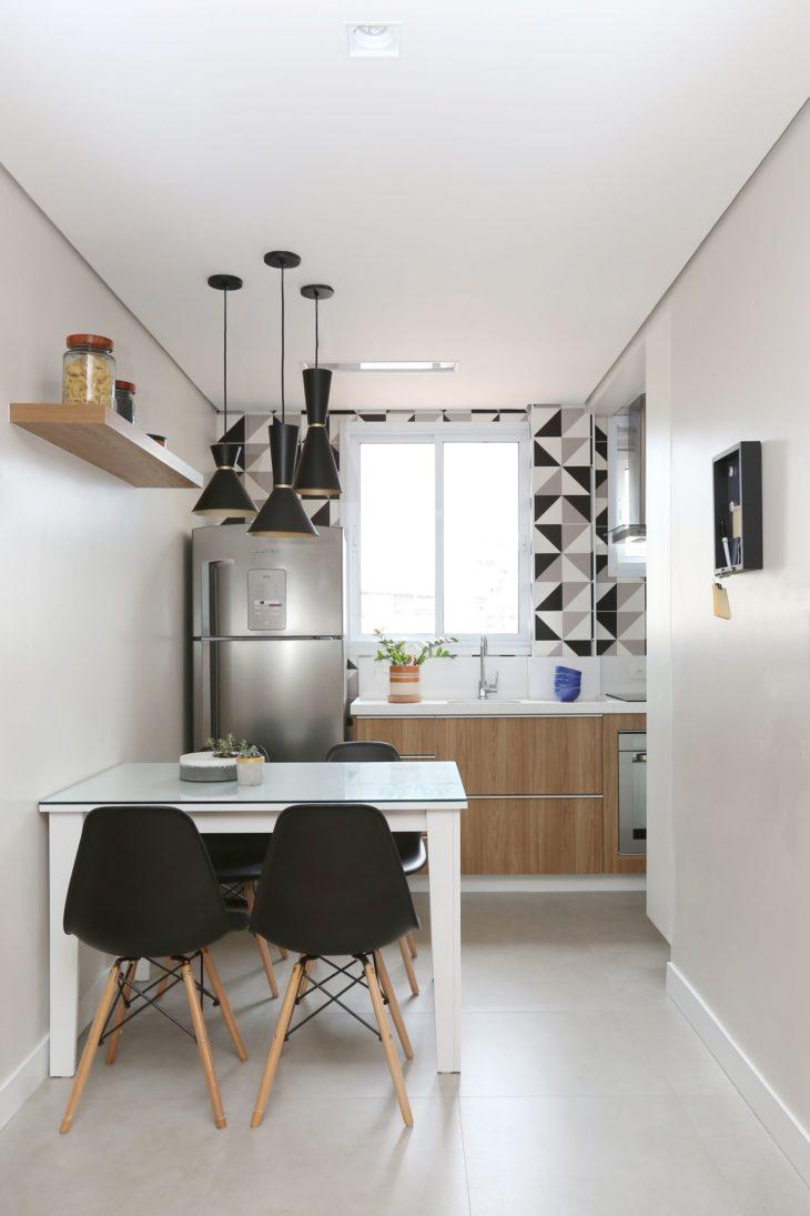 Decoração simples com azulejo preto e branco e mesa de madeira branca.