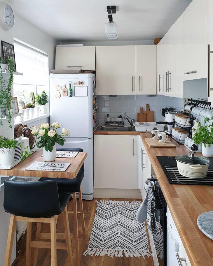 Cozinha pequena branca com mesa de madeira.