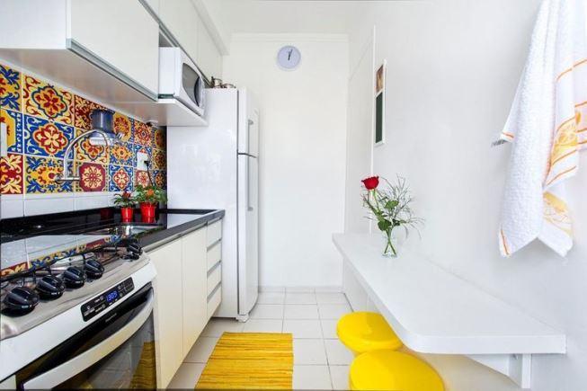 Cozinha pequena com bancada branca e azulejo decorado.