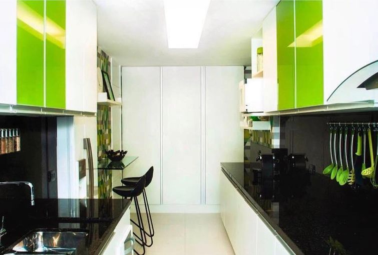 Cozinha pequena com armário verde.