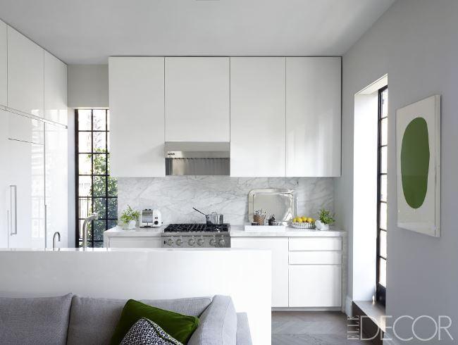 Decoração moderna com armário branco e acabamento de mármore.