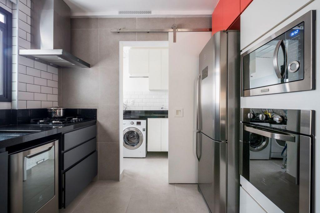 Cozinha pequena moderna com armário preto e azulejo de tijolinho branco.