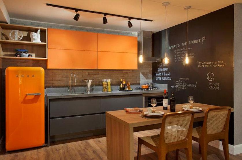 Cozinha pequena moderna com armário laranja e parede de tijolinho aparente.