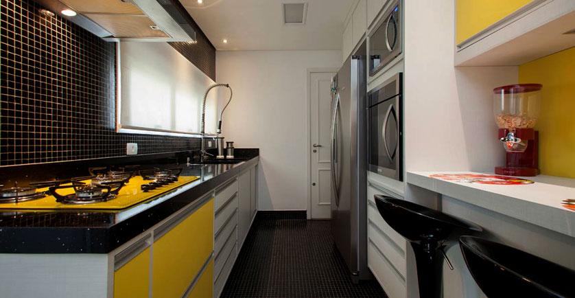 Cozinha pequena  com armário amarelo e pastilhas de cerâmica preta.