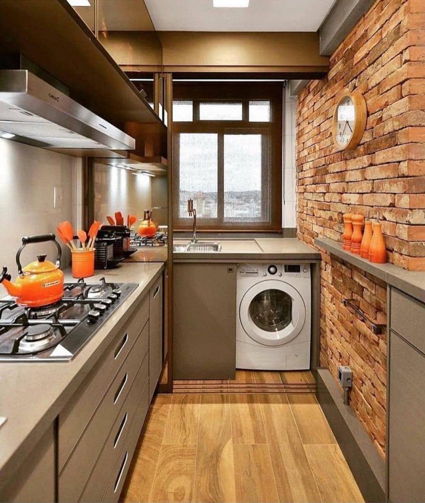 Cozinha pequena moderno com armário neutro e parede de tijolinho aparente.