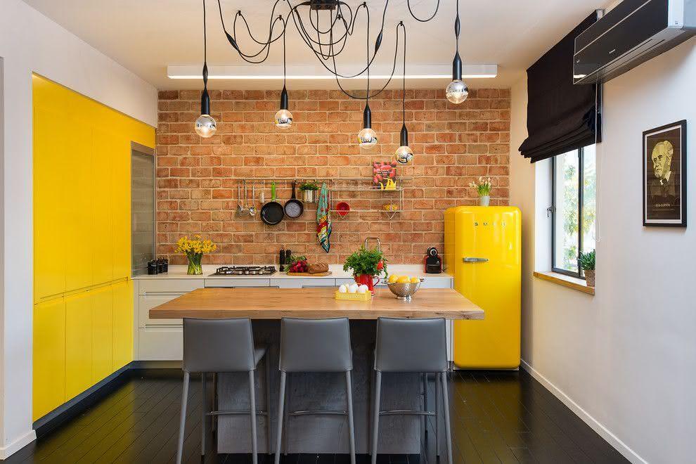 Decoração moderna com armário amarelo e parede de tijolinho aparente.