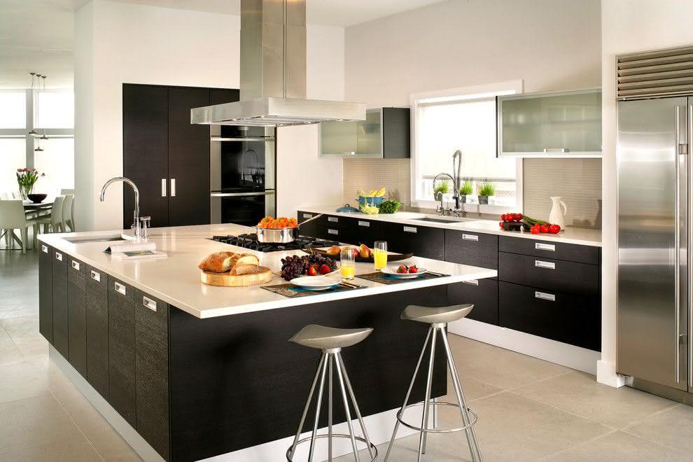 Decoração com armários pretos, bancada branca e cooktop.