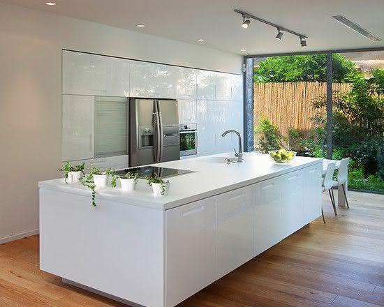 Decoração simples com bancada branca e cooktop.