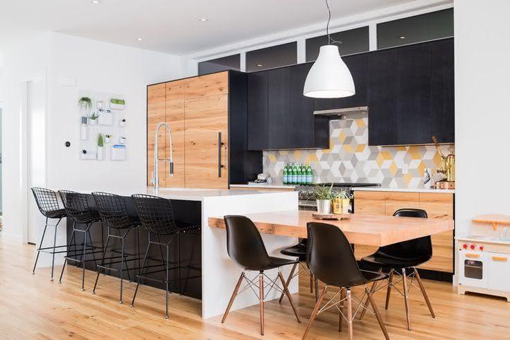 Decoração moderna com armários de madeira, bancada branca e mesa de madeira.