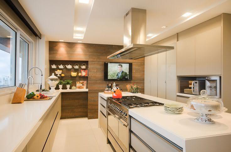 Decoração moderna com fogão no centro e coifa.