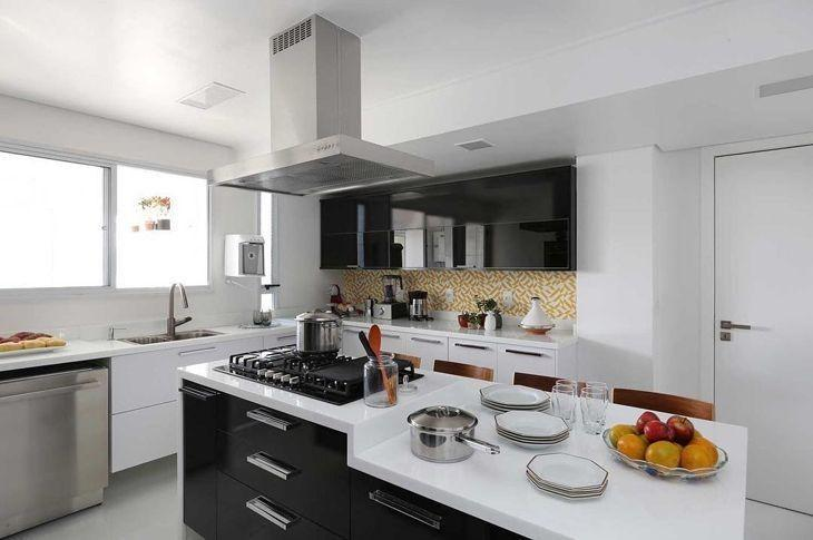 Decoração preta e branco com armários simples, cooktop e coifa.