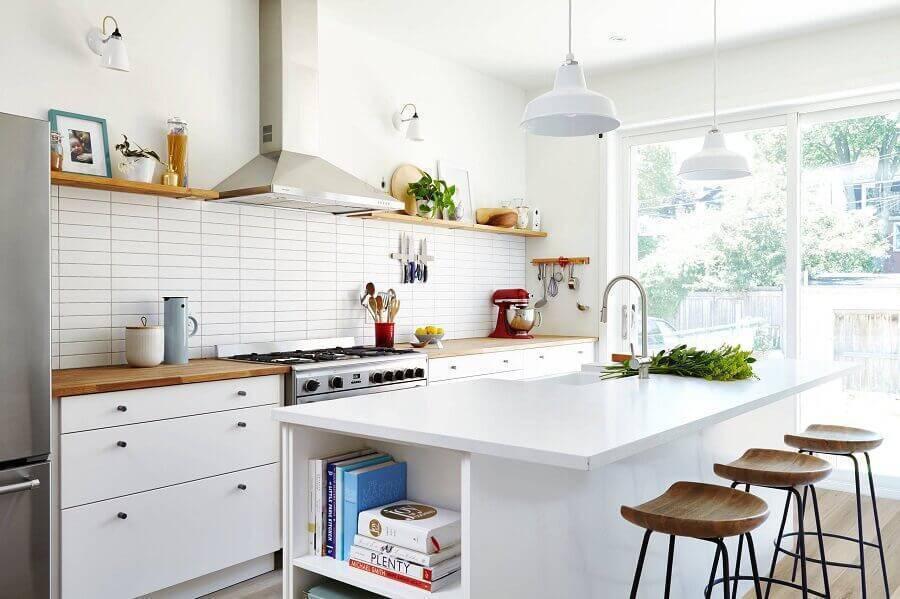 Decoração simples com bancada de madeira e azulejo de tijolinho branco.