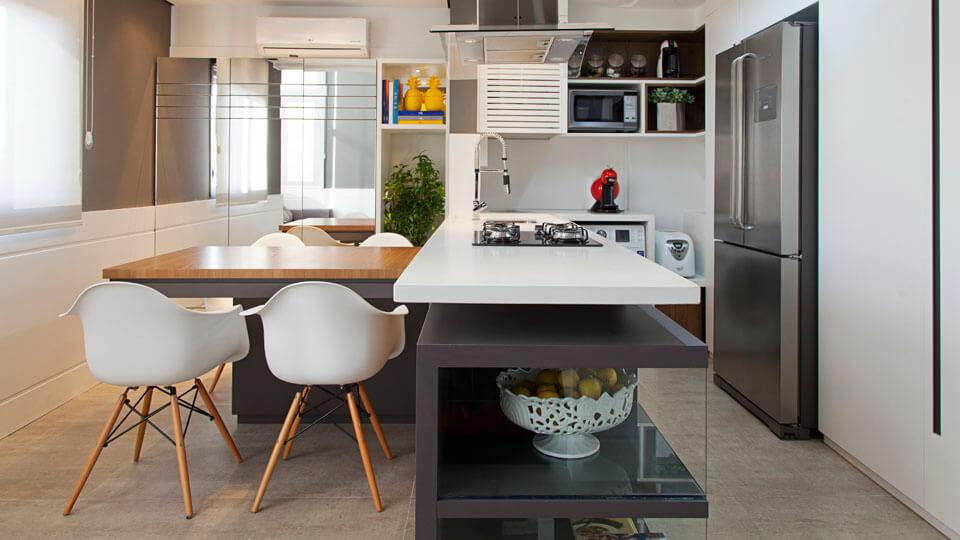 Cozinha planejada com ilha simples e mesa de madeira.
