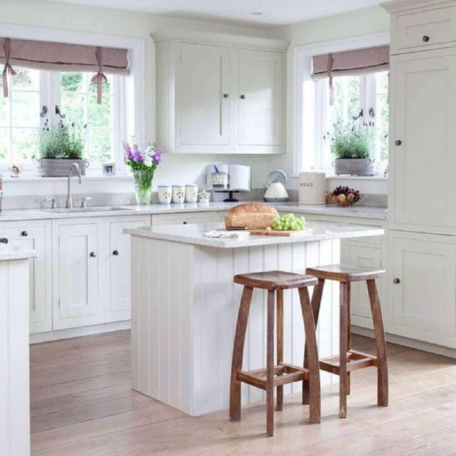Cozinha planejada com ilha simples e branca.