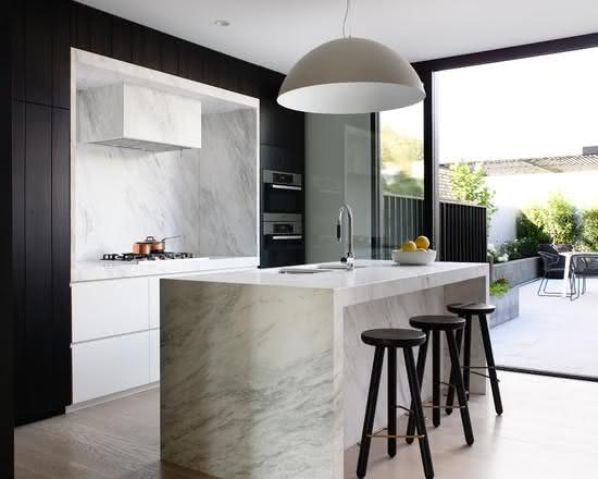 Decoração moderna com armário preto e bancada de mármore.