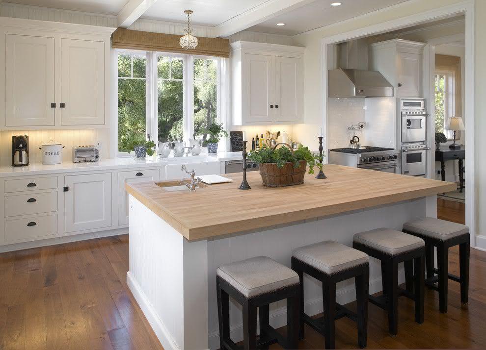 Cozinha planejada com ilha grande com bancada de madeira.