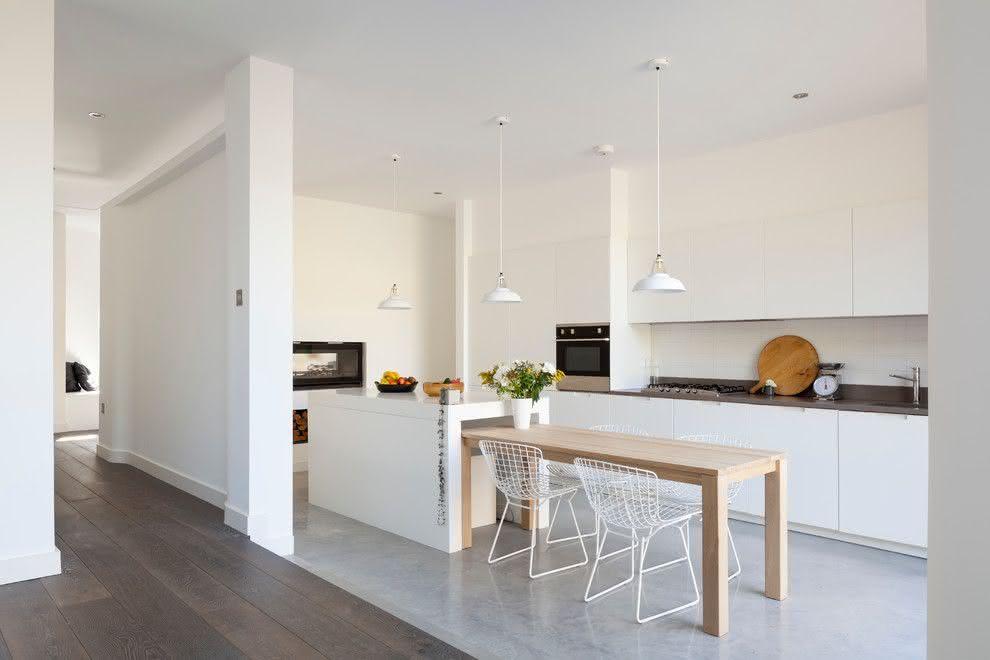 Cozinha planejada com ilha moderna e mesa de madeira.