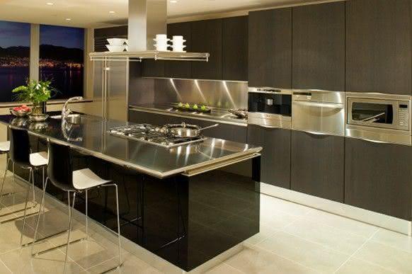 Cozinha planejada com ilha com bancada de inox.
