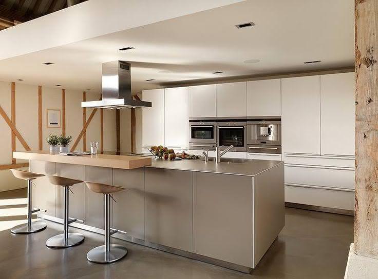Cozinha planejada com ilha com bancada de madeira.
