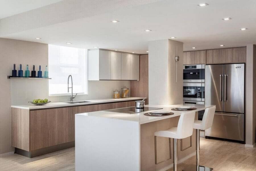 Cozinha planejada com ilha com cooktop.
