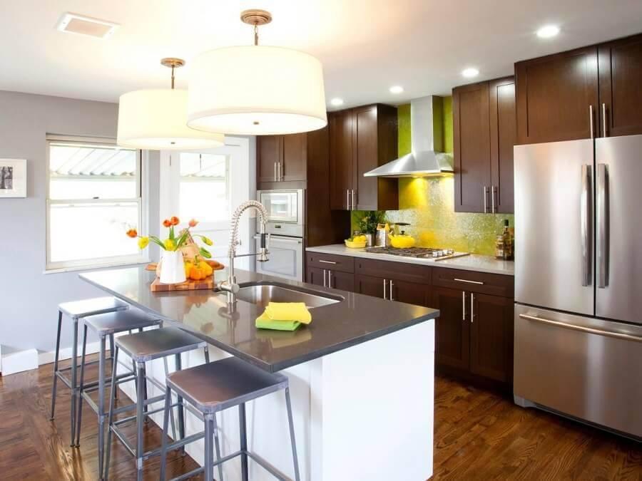 Cozinha planejada com ilha com pia e troneira moderna.