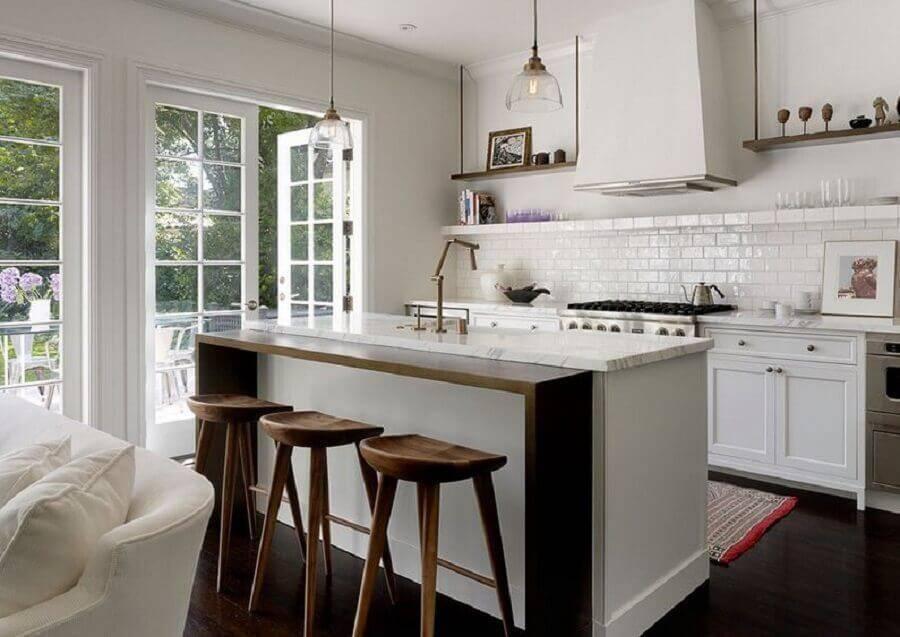 Cozinha planejada com ilha com pia e bancada de madeira.