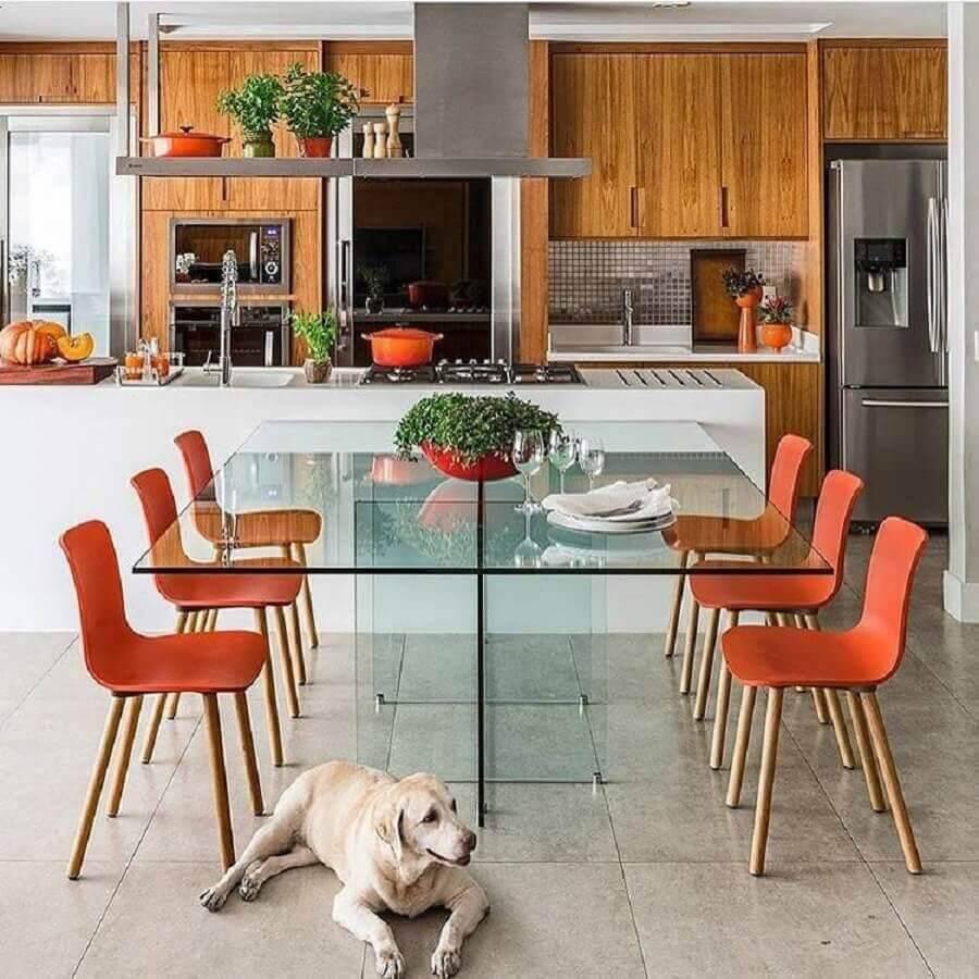 Cozinha planejada com ilha moderna e mesa de vidro.