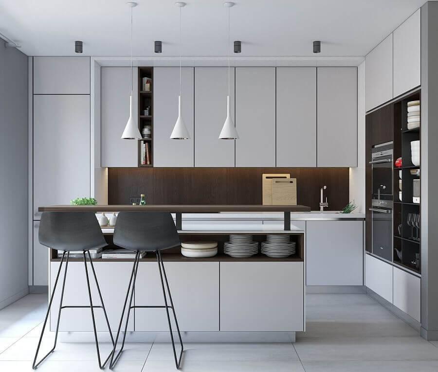 Cozinha planejada com ilha moderna e banquetas pretas.