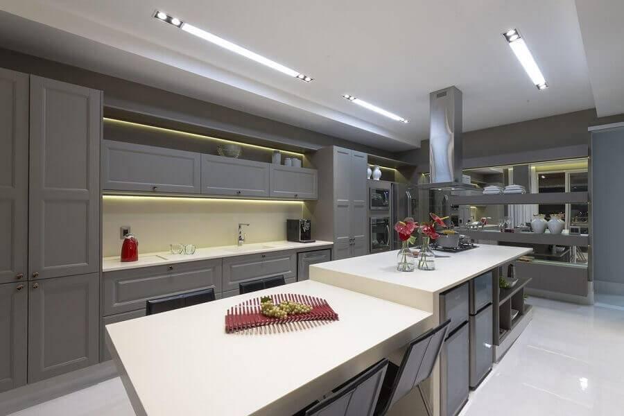Cozinha planejada com ilha moderna e com bancada branca.