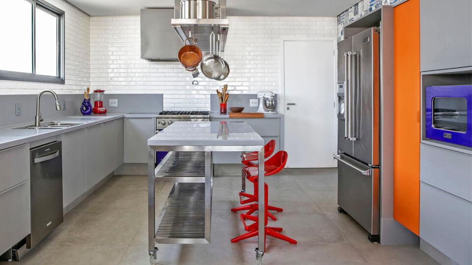 Cozinha planejada com ilha de aço inox.